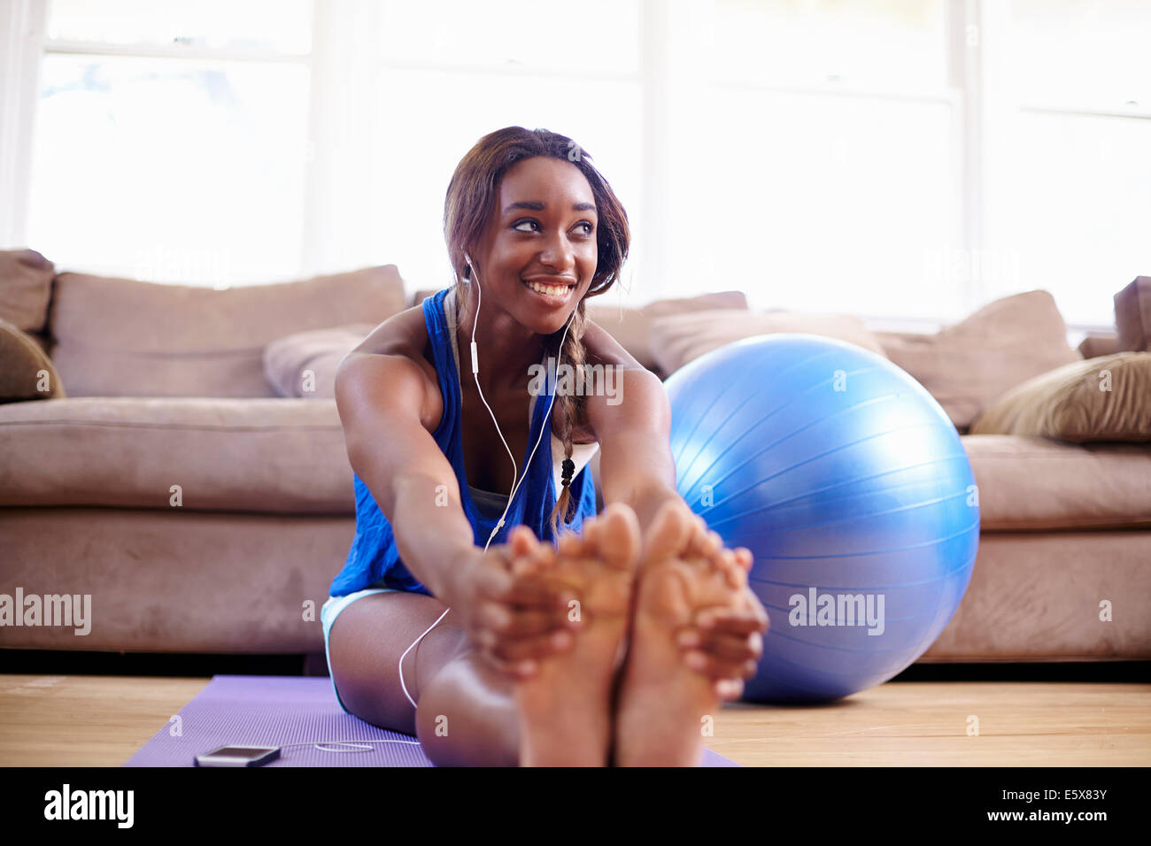Young woman exercising and touching toes on sitting room floor - Stock Image