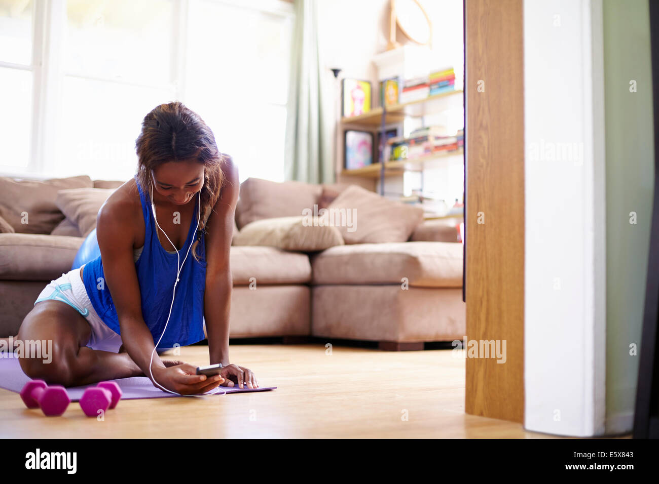 Young woman exercising on sitting room floor whilst looking at smartphone Stock Photo