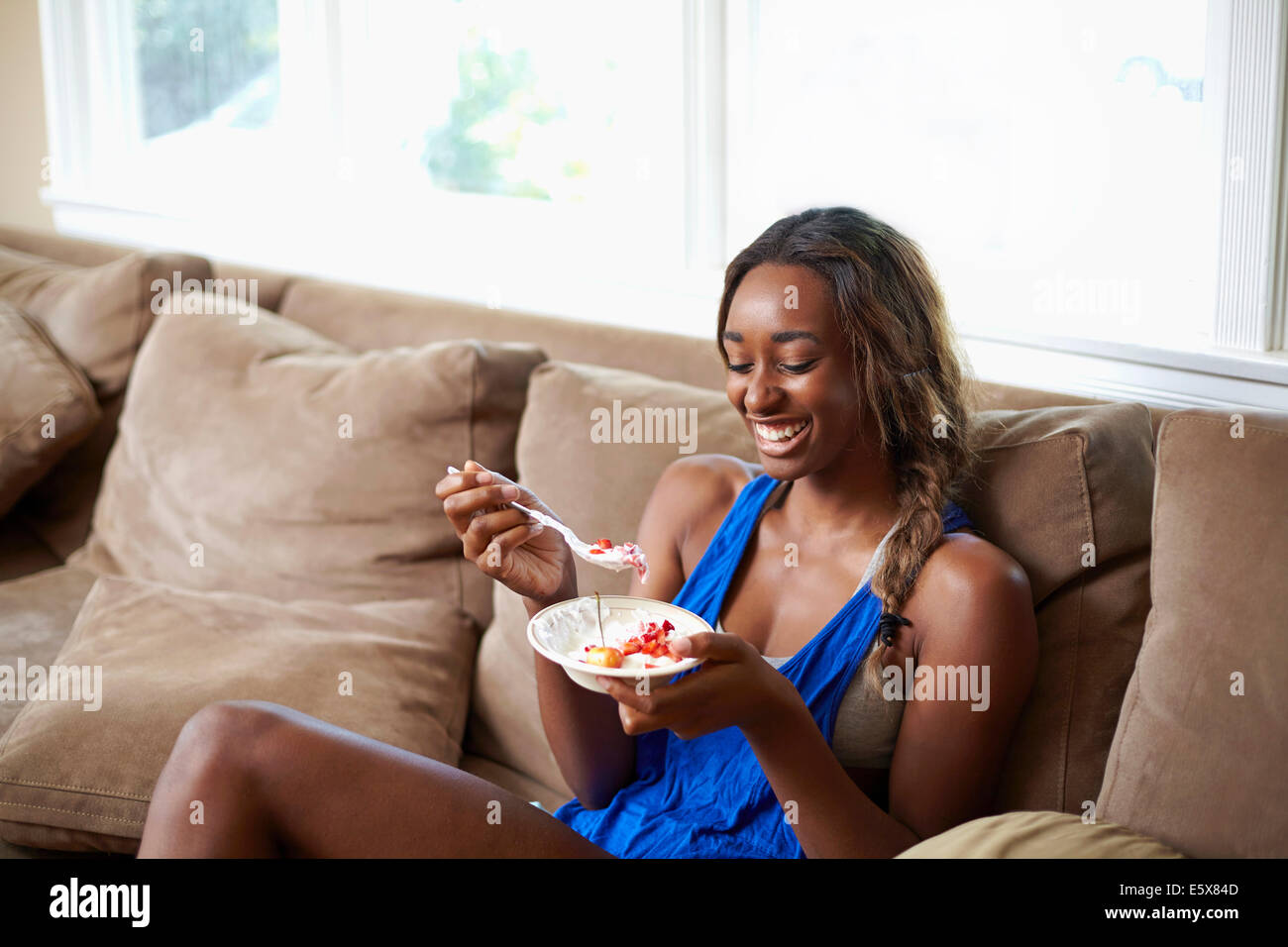 Young woman taking a training break, eating fruit on sofa - Stock Image