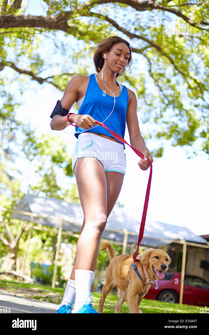 Young woman exercising with dog in park - Stock Image