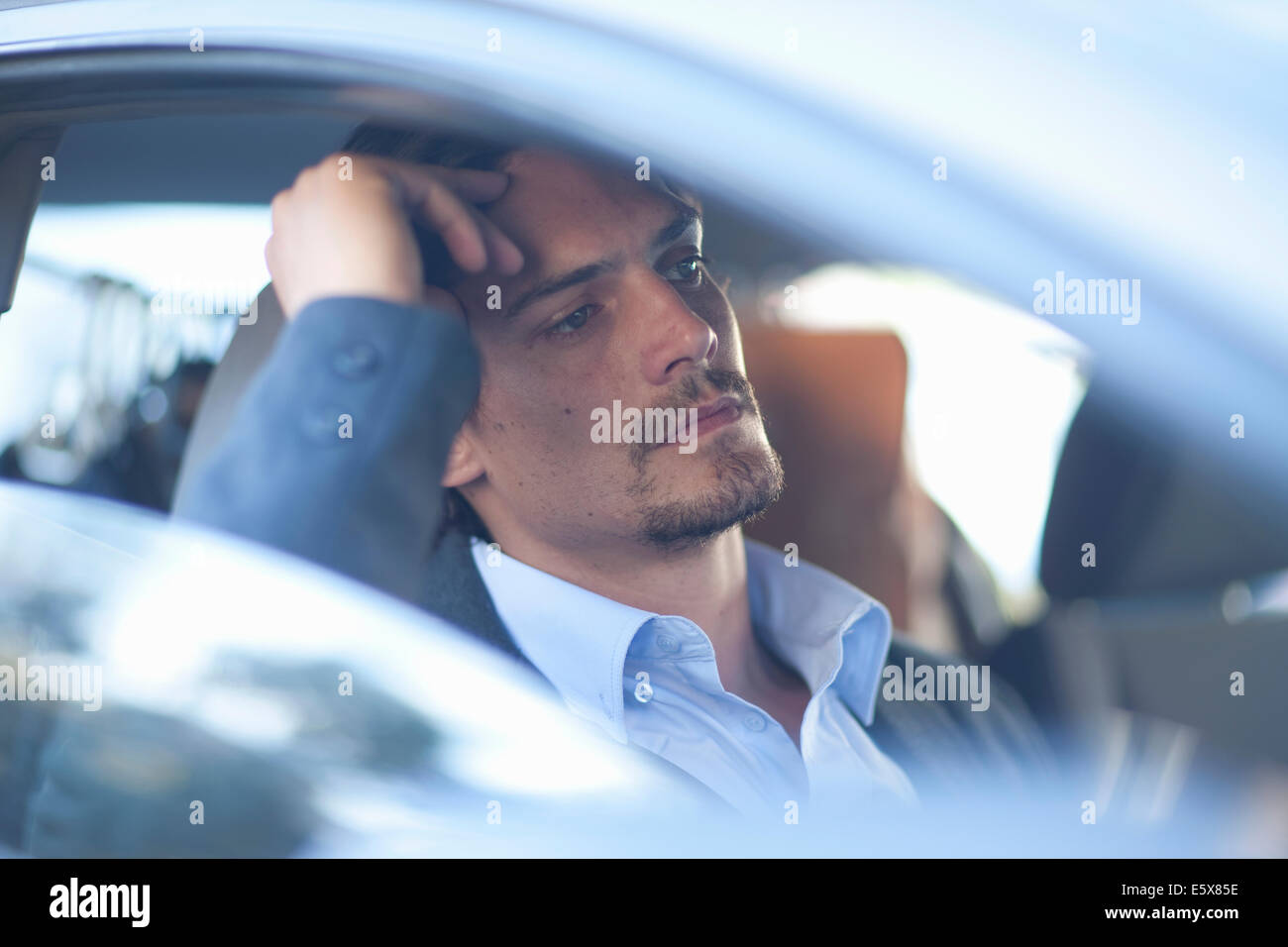 Mid adult businessman driving in traffic congestion - Stock Image