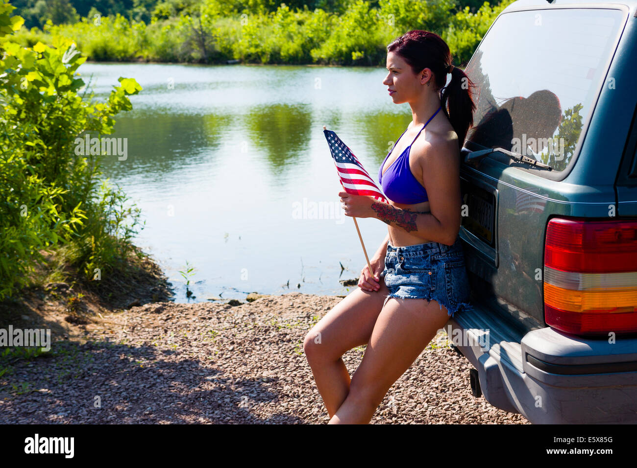 Young woman with american flag leaning against off road vehicle, Delaware Canal State Park, New Hope, Pennsylvania, - Stock Image