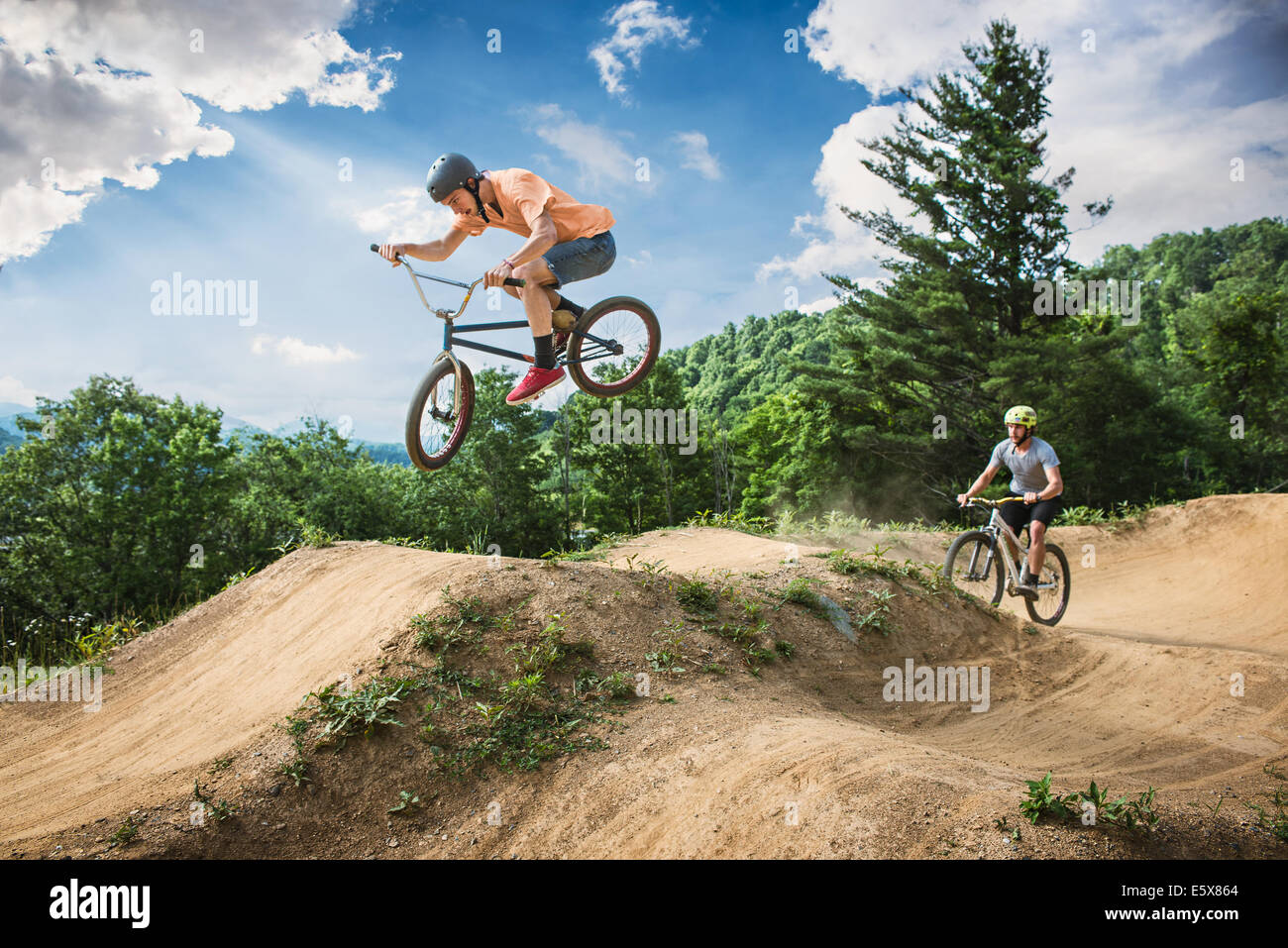 Two male friends riding BMX and mountain bikes on rural pump track Stock Photo