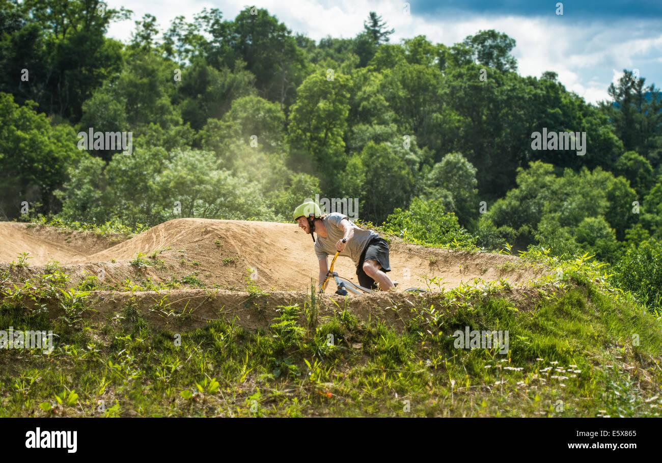 Mountain biker speeding around bend on rural pump track - Stock Image
