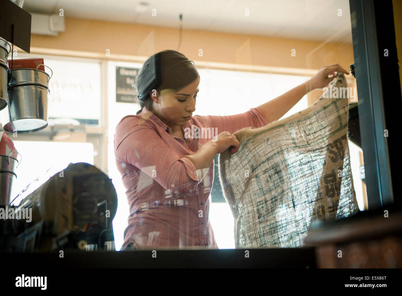 Young woman holding up empty sack used for coffee roasting machine in cafe - Stock Image