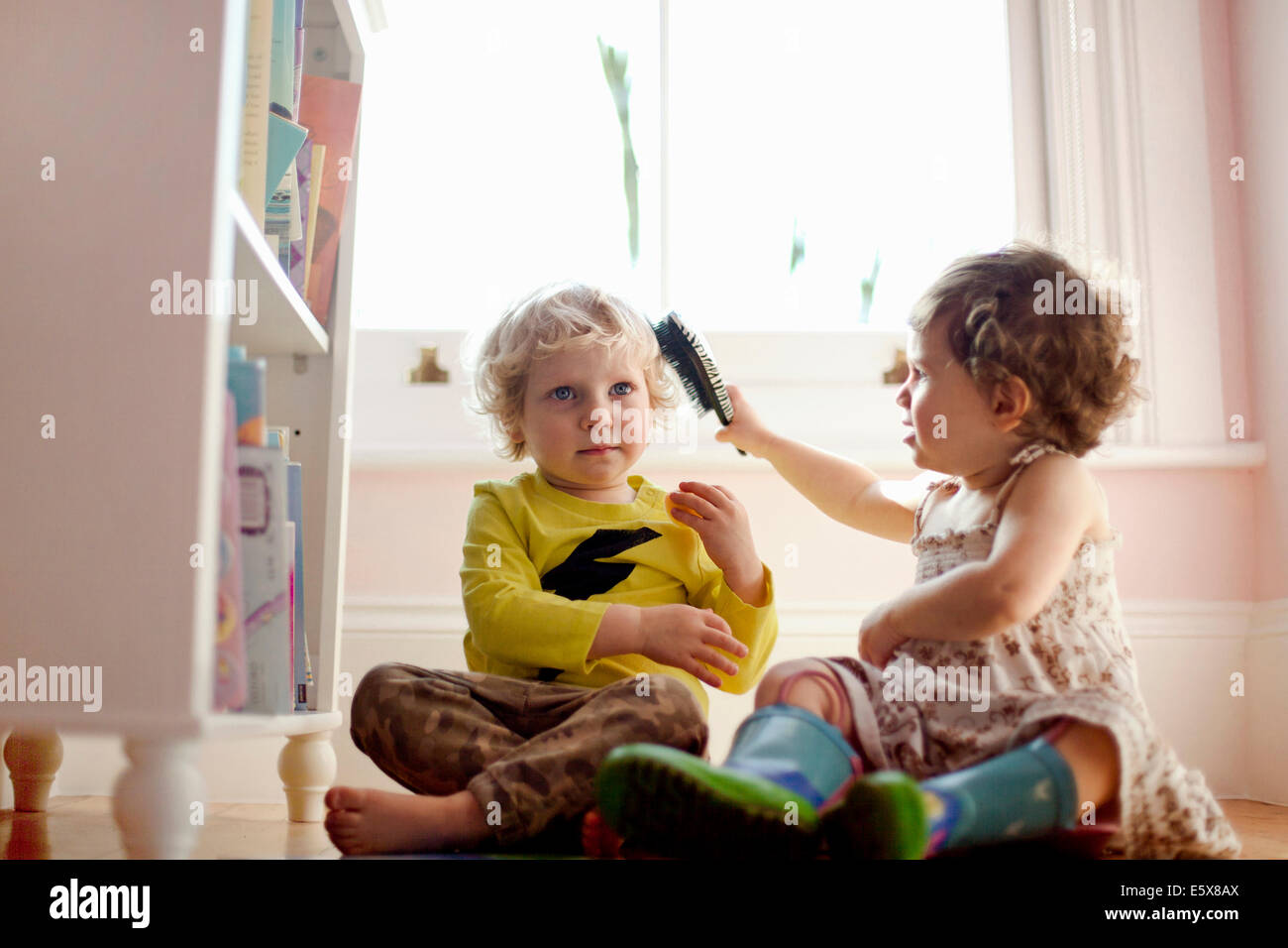 Female toddler brushing male toddlers hair in playroom - Stock Image
