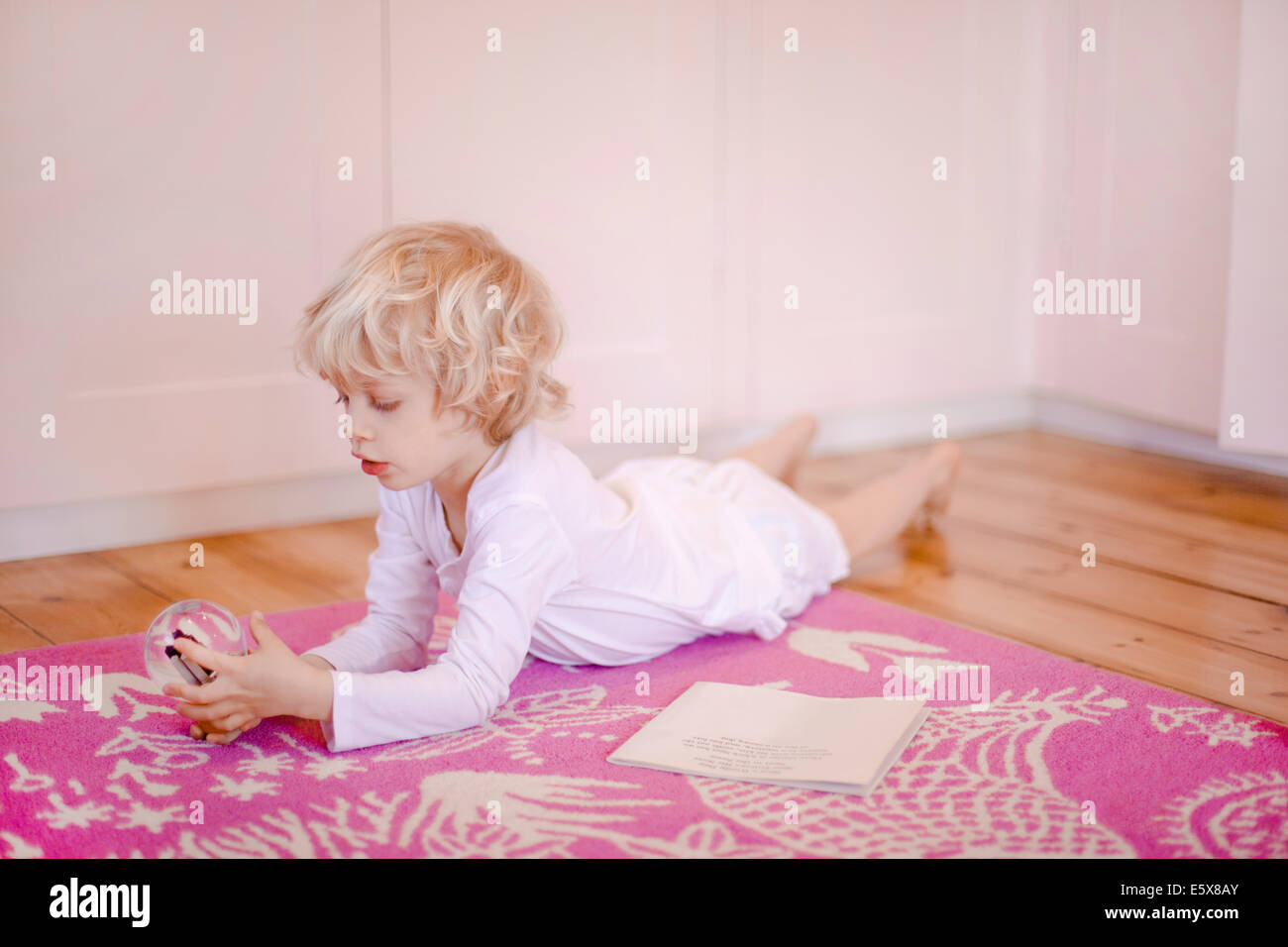 Four year old boy lying on rug gazing at snow globe - Stock Image