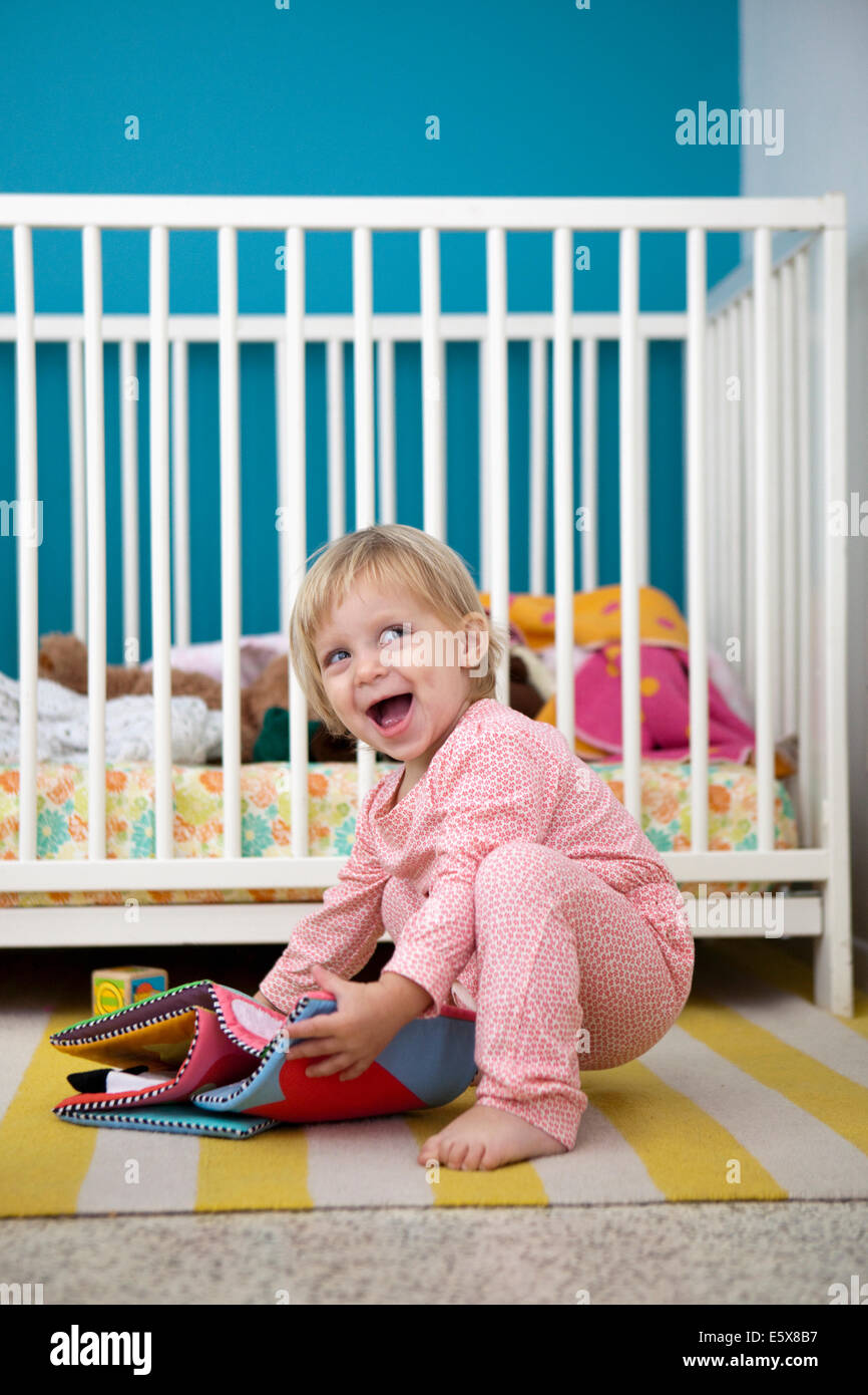 Female toddler playing with textile picture book in bedroom - Stock Image