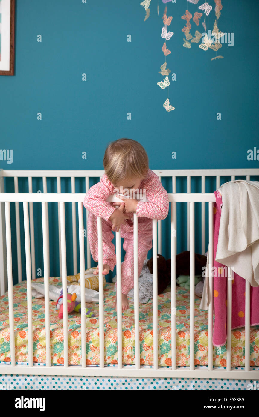 Female toddler climbing over side of crib - Stock Image
