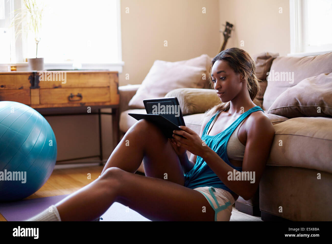 Young woman taking a training break, looking at digital tablet in sitting room - Stock Image