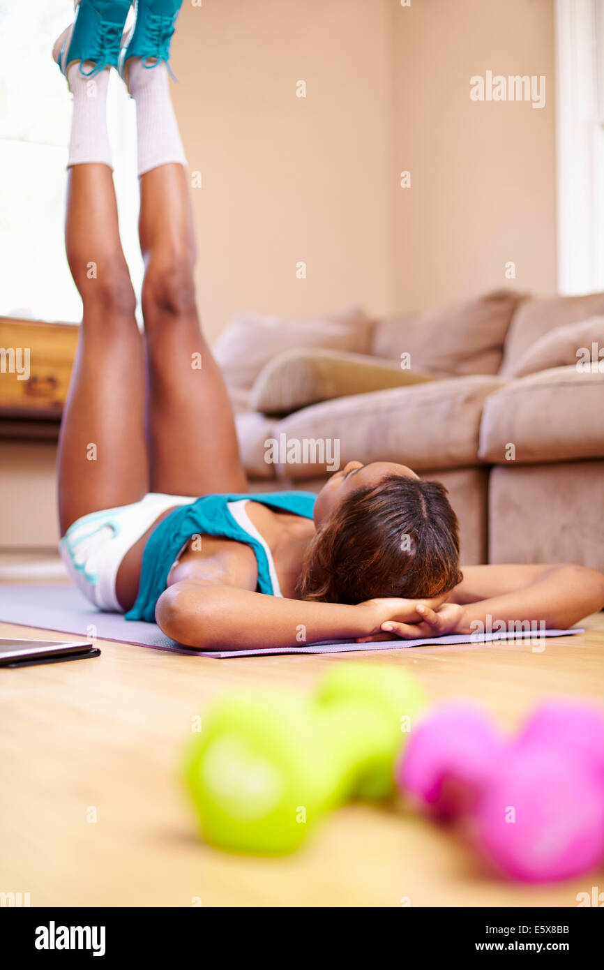 Rear view of young woman exercising on sitting room floor Stock Photo