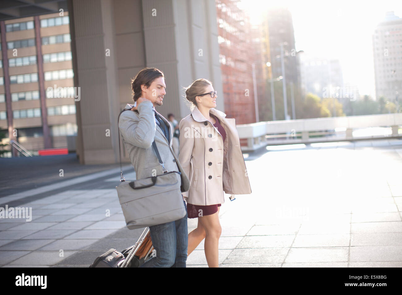 Businessman and woman walking across city rooftop parking lot - Stock Image