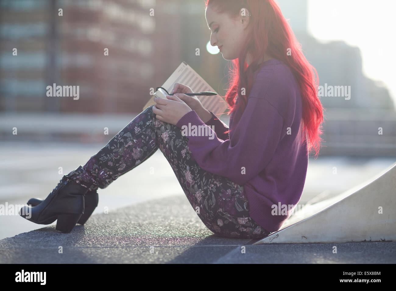 Young woman writing in notebook on city rooftop parking lot - Stock Image