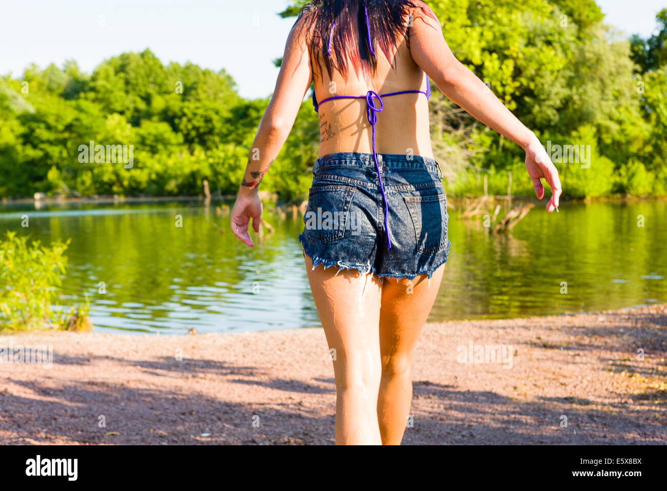 Rear cropped view of young woman walking toward canal, Delaware Canal State Park, New Hope, Pennsylvania, USA - Stock Image