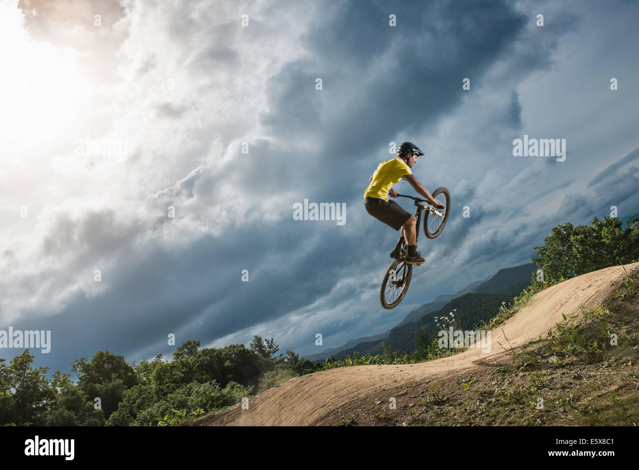 Young male mountain biker jumping mid air on rural pump track - Stock Image