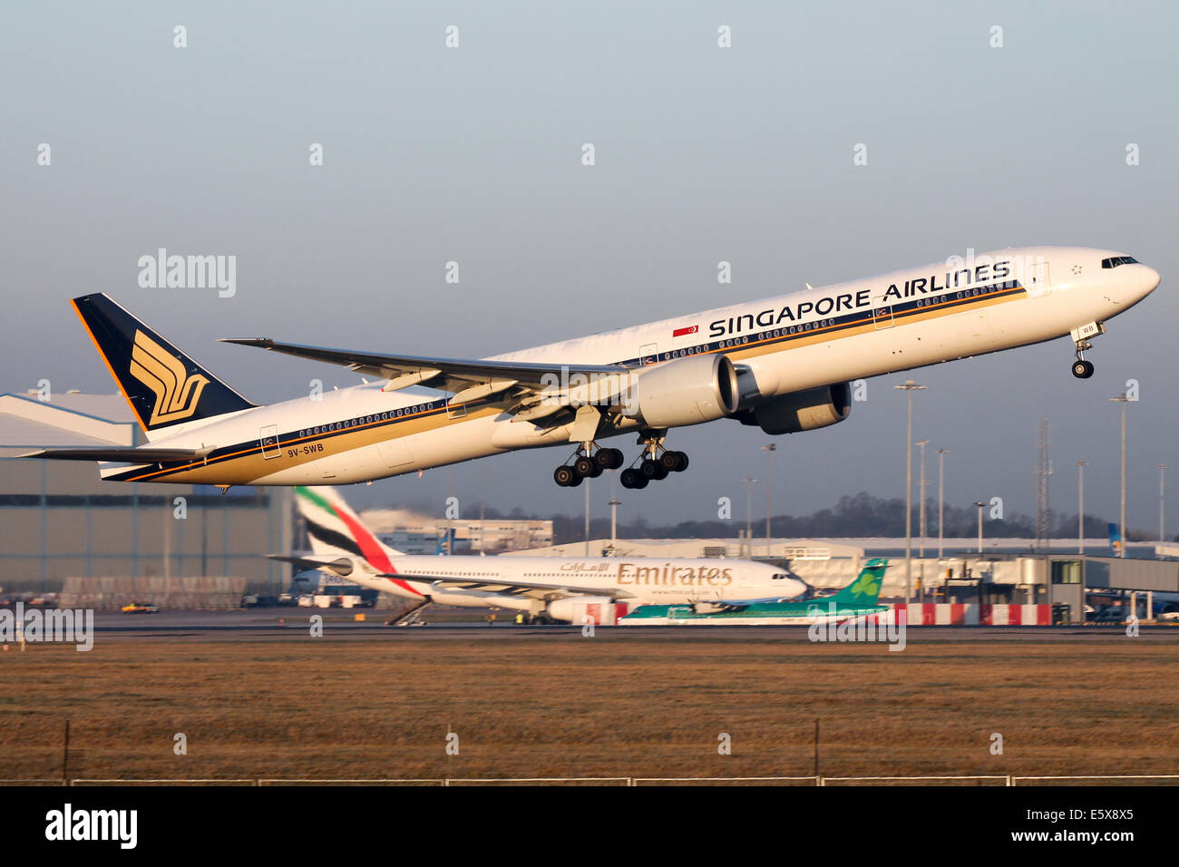 Singapore Airlines Boeing 777-300ER climbs away from runway 05L at Manchester airport. Stock Photo
