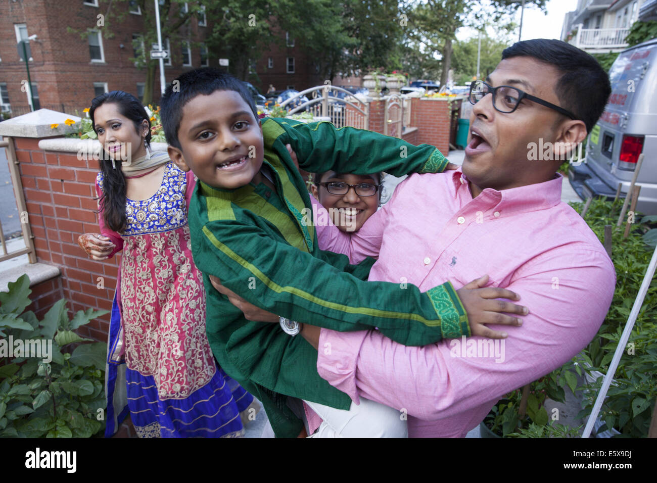 Uncle has fun with his nephew at a family gathering of Bangladeshi Americans on the Muslim holiday of Eid in Brooklyn, - Stock Image