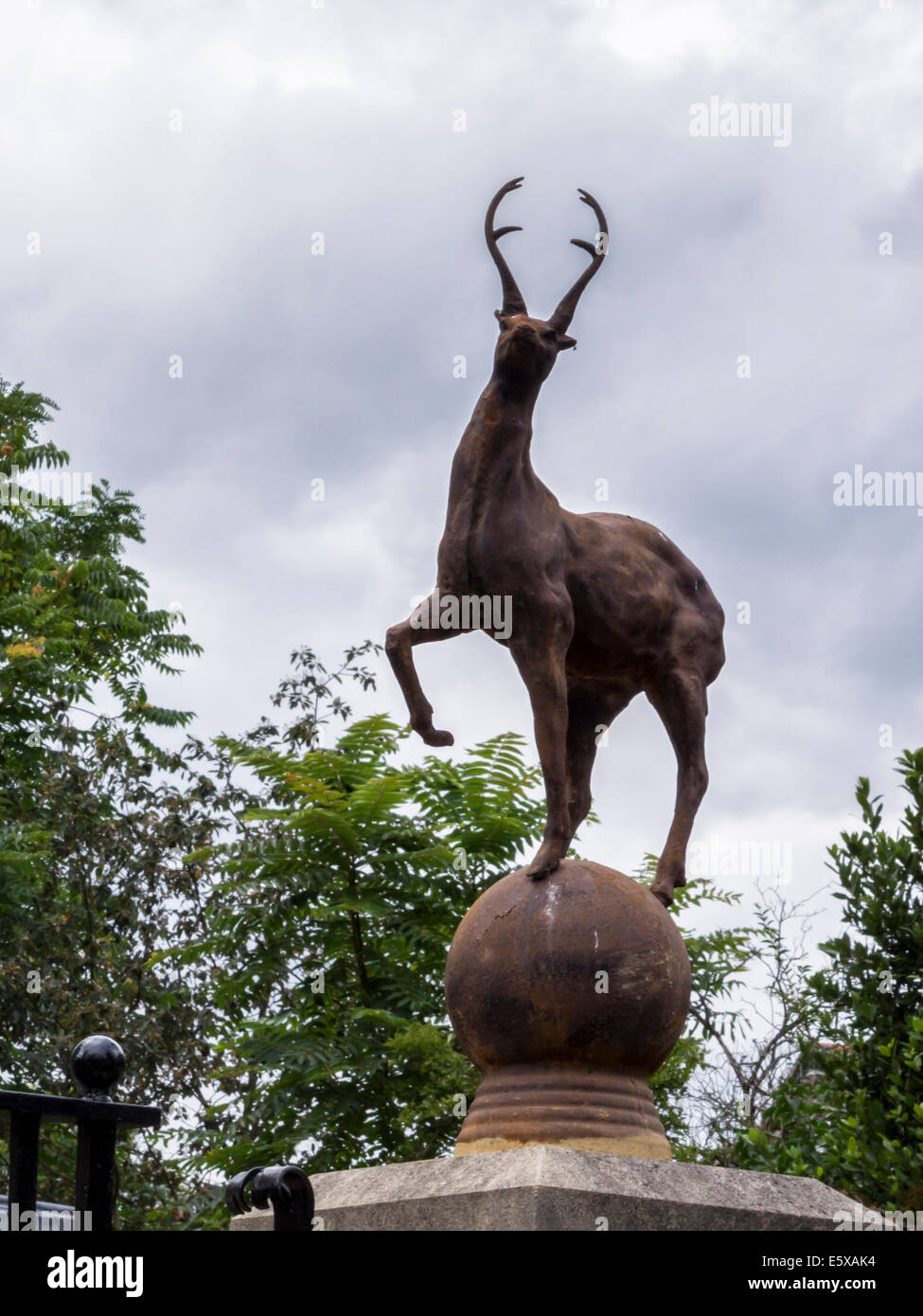 Deer standing on pillar of a gatepost of a home against a cloudy sky - East Twickenham, London TW9 - Stock Image
