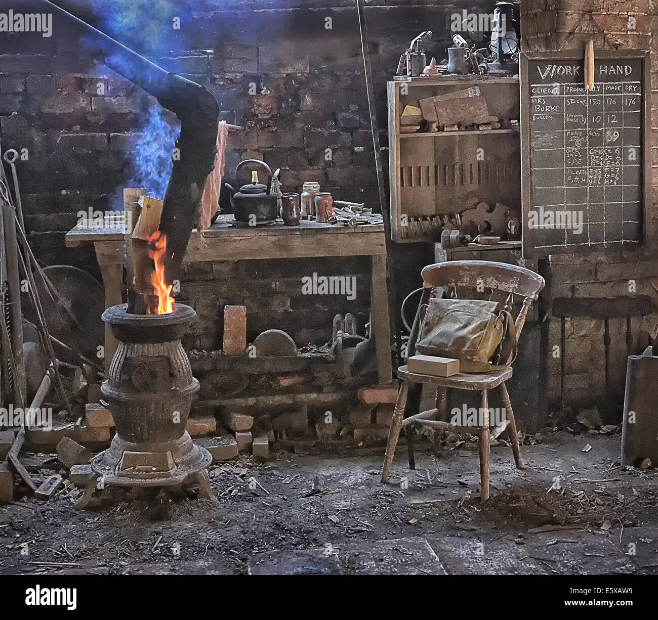 old workshop with pot bellied stove and chair - Stock Image