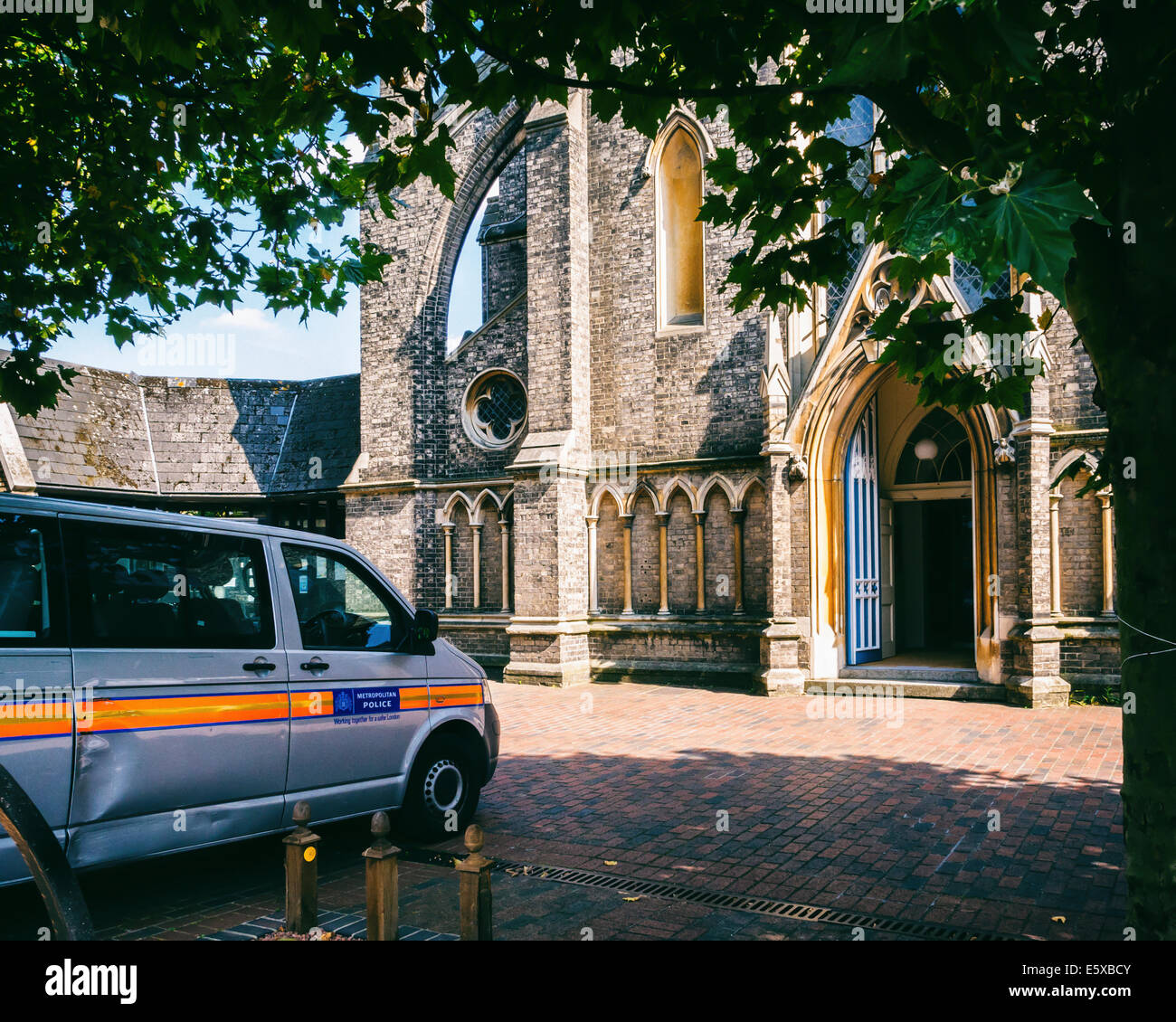 St. John the Divine Grade11 listed church in early Gothic Revival architectural style and parked police van - Richmond, - Stock Image