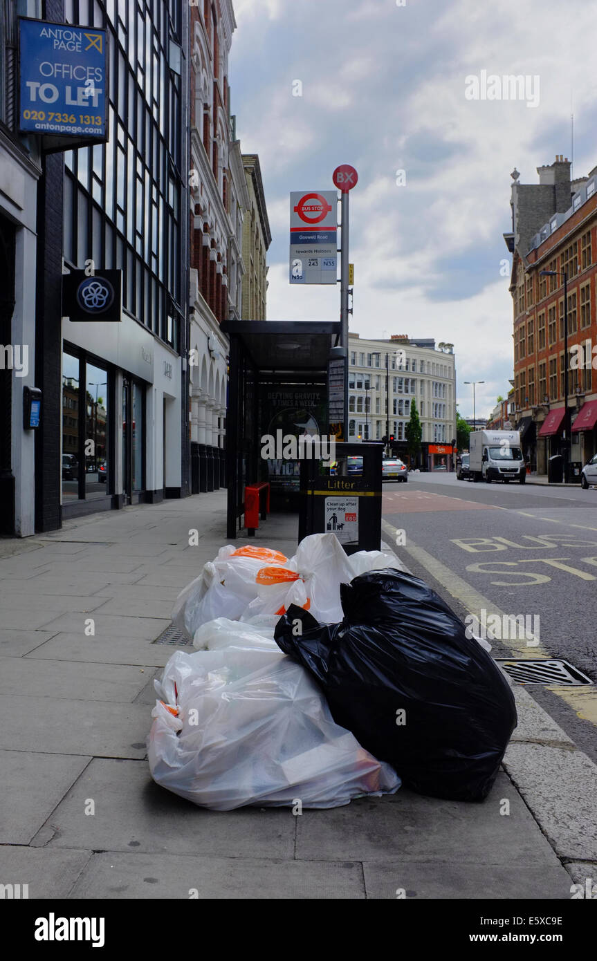 rubbish bags left in street by bus stop - Stock Image
