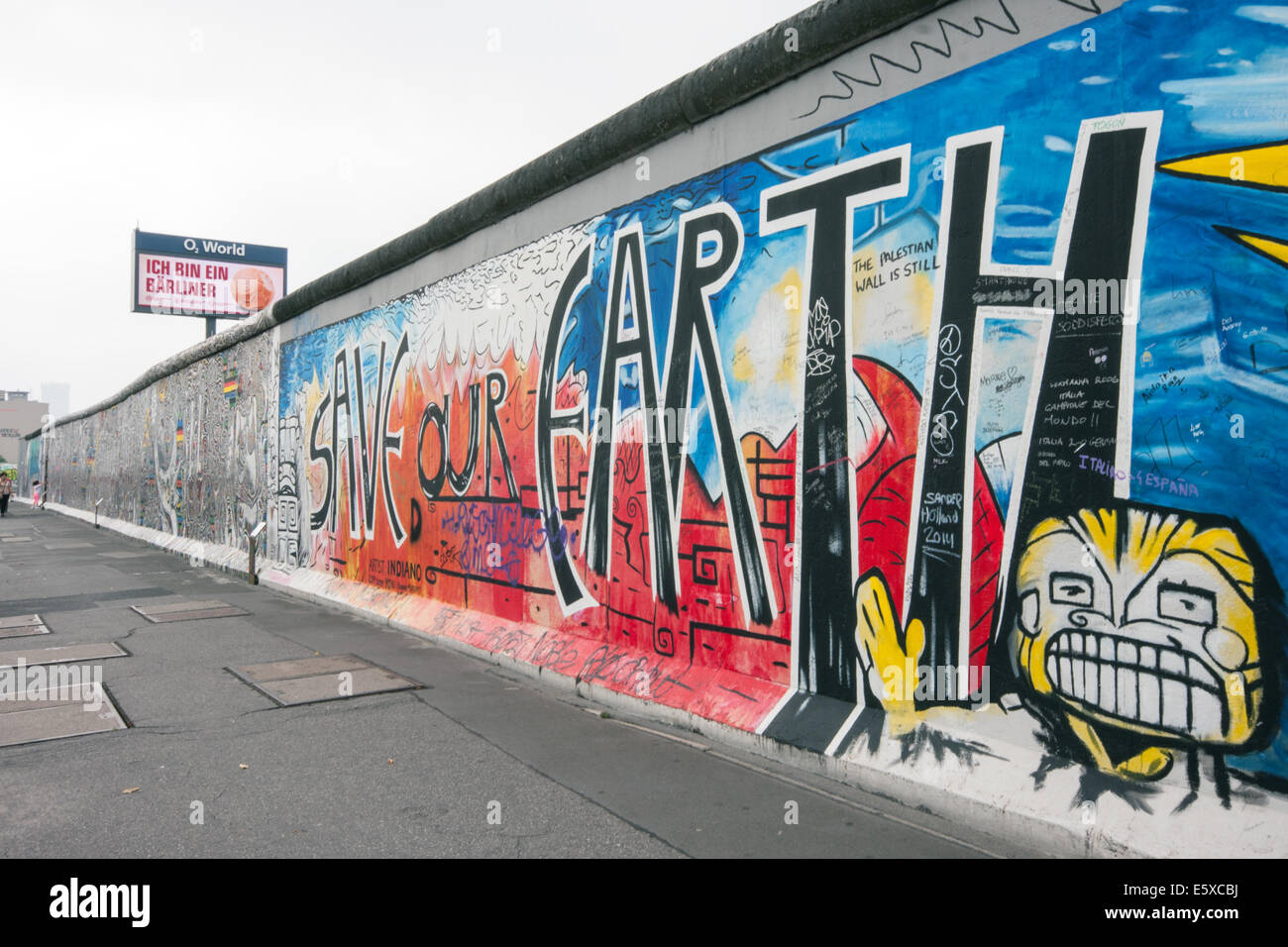 Save our earth artwork on berlin wall at east side gallery beneath an o2 advertisement screen