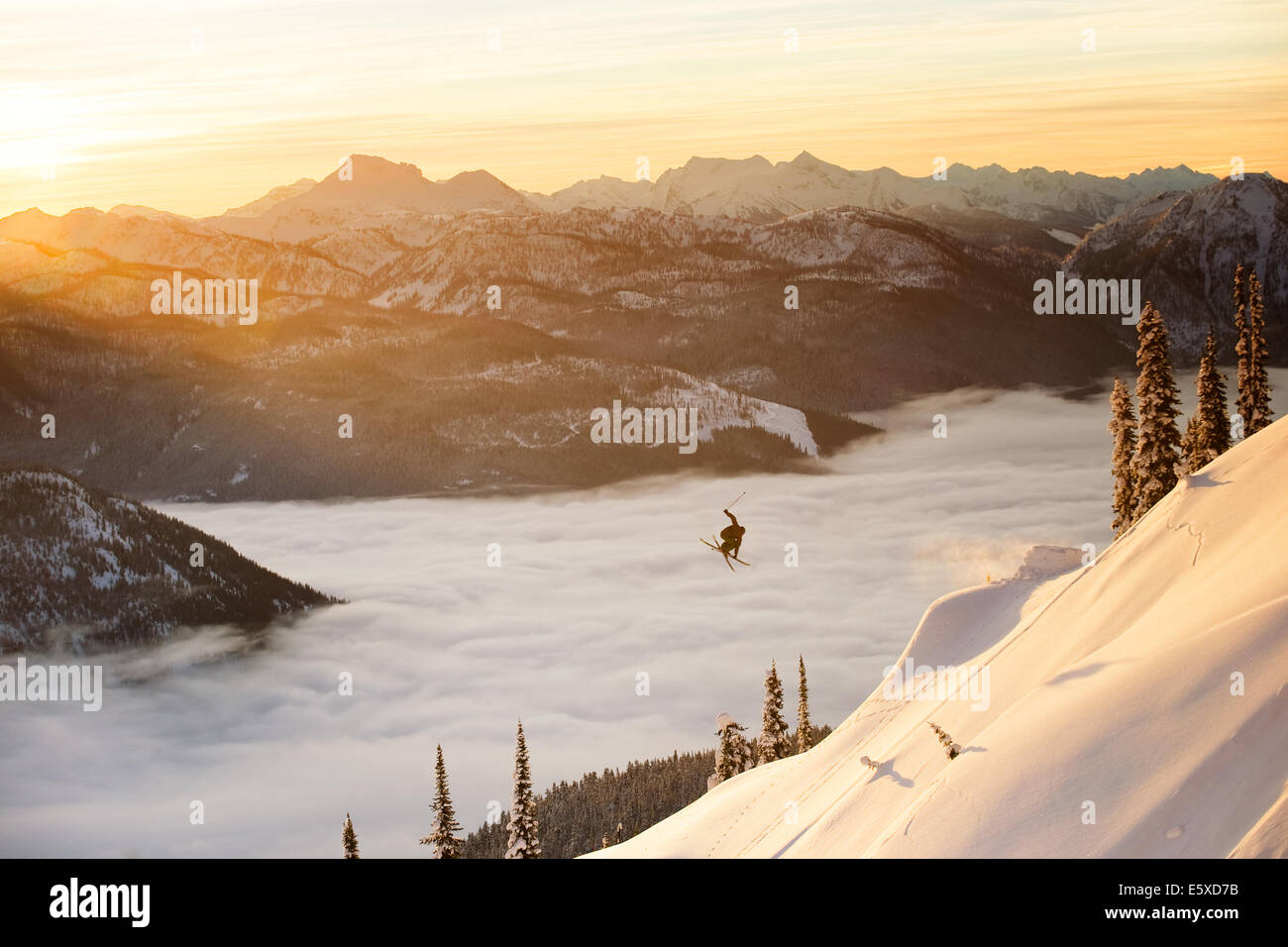 Mark Abma hitting a jump while skiing in the Mustang Powder Cats mountain area, B.C., Canada at sunset - Stock Image