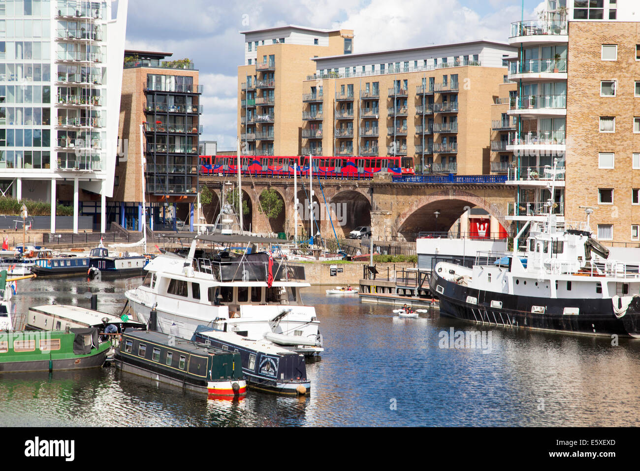 Limehouse Basin in East London on a sunny day - DLR train in the background, Pinnacle I building on the left and Stock Photo