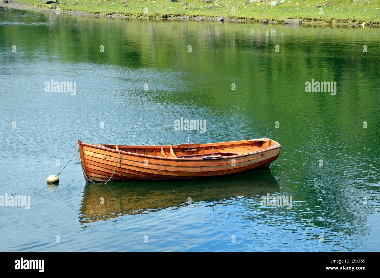A small clinker built wooden rowing boat tied to a mooring buoy in the harbour at Westport Quay, Mayo, Ireland. - Stock Image