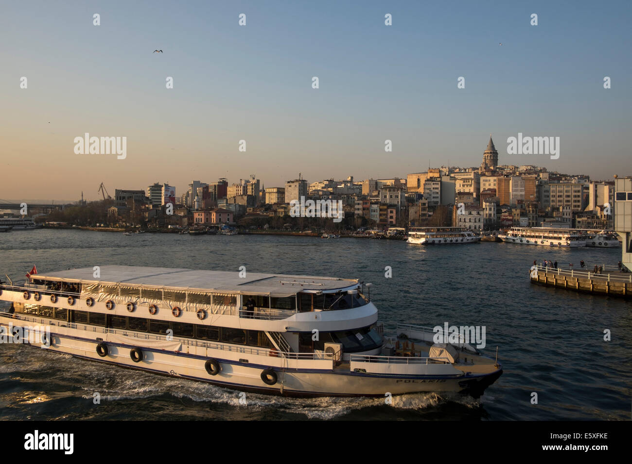 A passenger ship floating on the Golden Horn as the Galata Tower stands out in the skyline in Istanbul, Turkey on - Stock Image