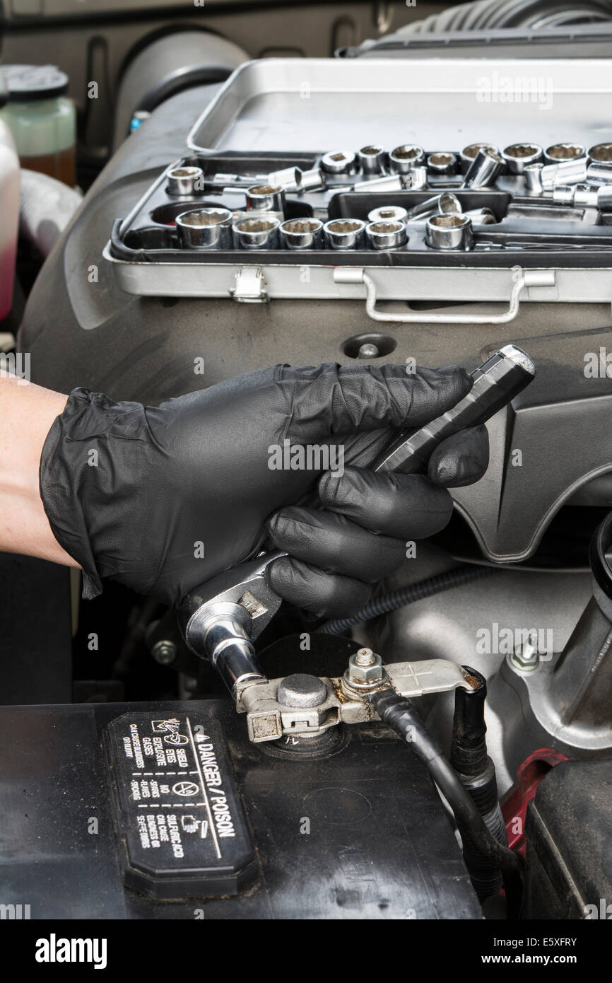 A mechanic tightens a battery terminal cable to a lead battery post. - Stock Image
