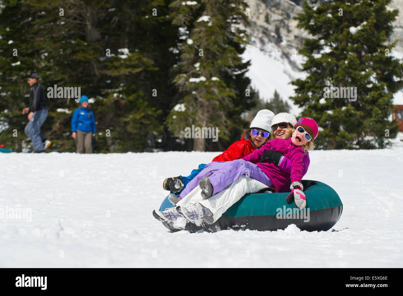 Julien, Suzanne and Lucy Weiss enjoy tubing at Snowbird Resort in Utah. - Stock Image