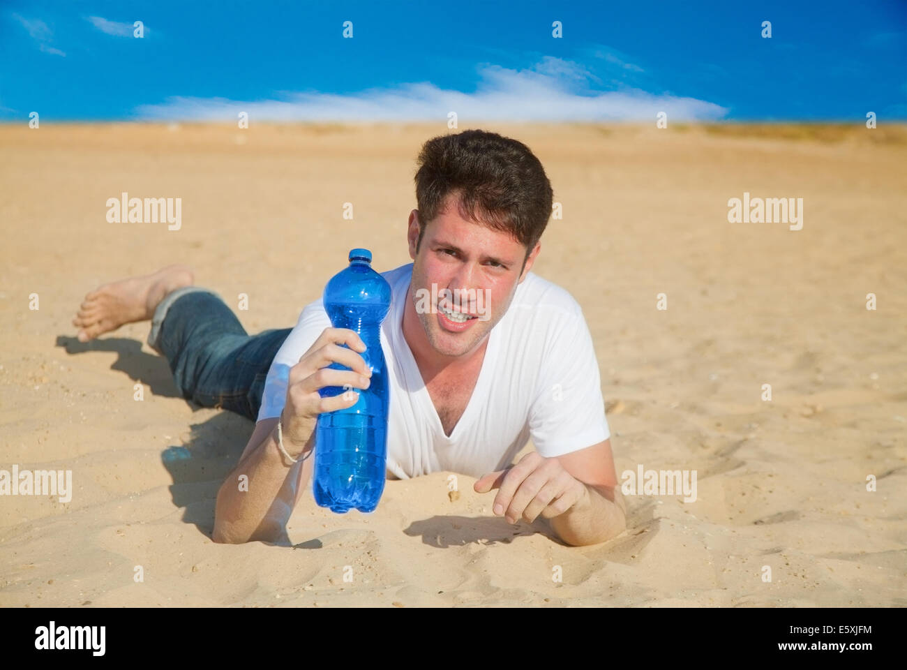 Caucasian man with a bottle of fresh water in desert - Stock Image