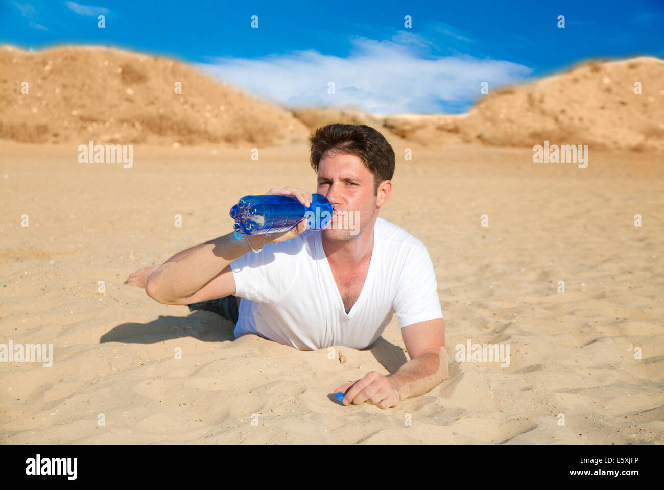 Thirsty man drinking water in the desert - Stock Image