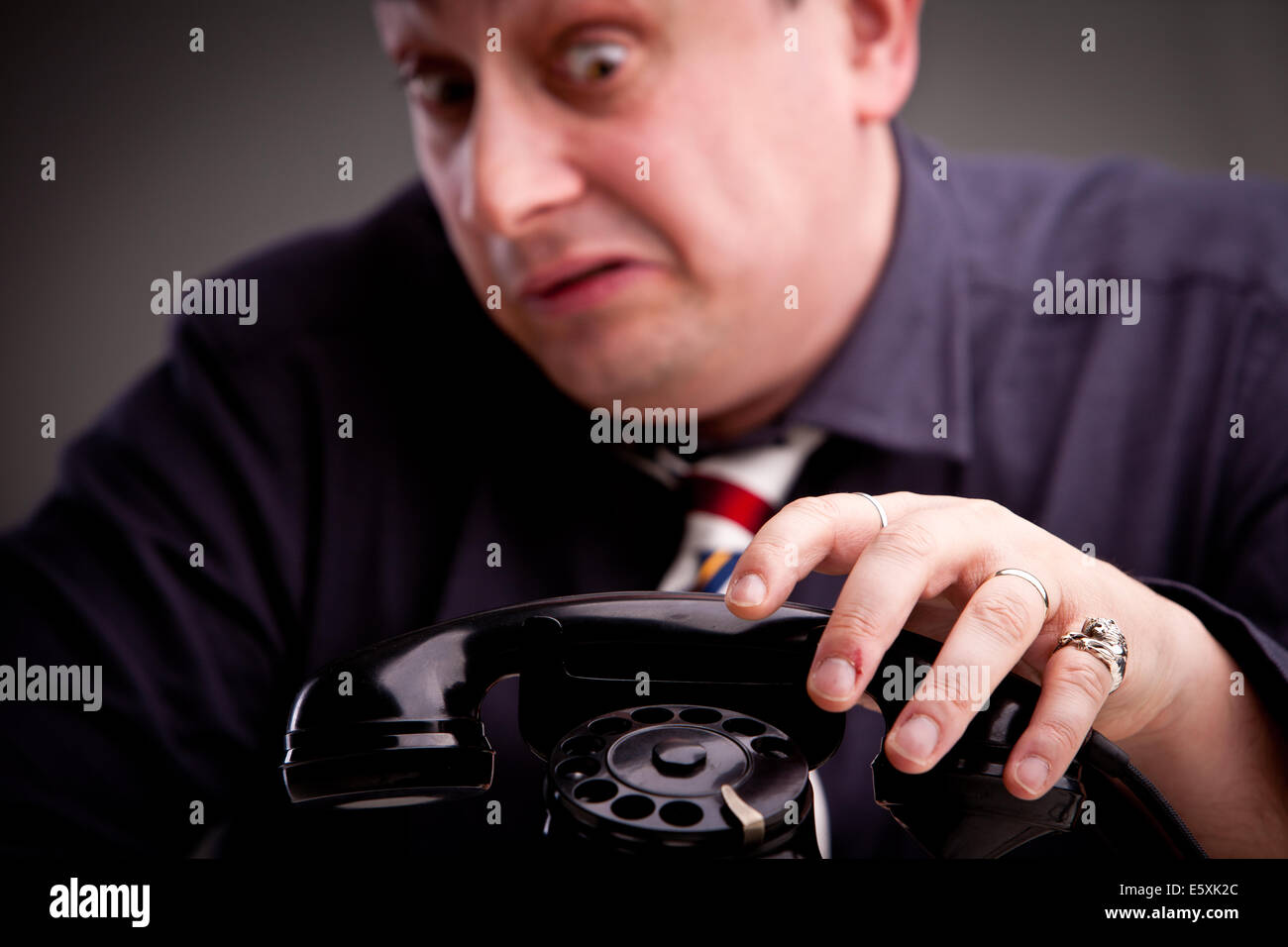 Telephone rings and the clerk is afraid of taking the call - Stock Image