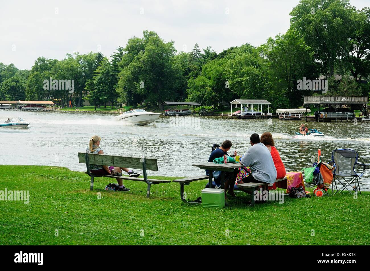 People picnicking along river bank. - Stock Image