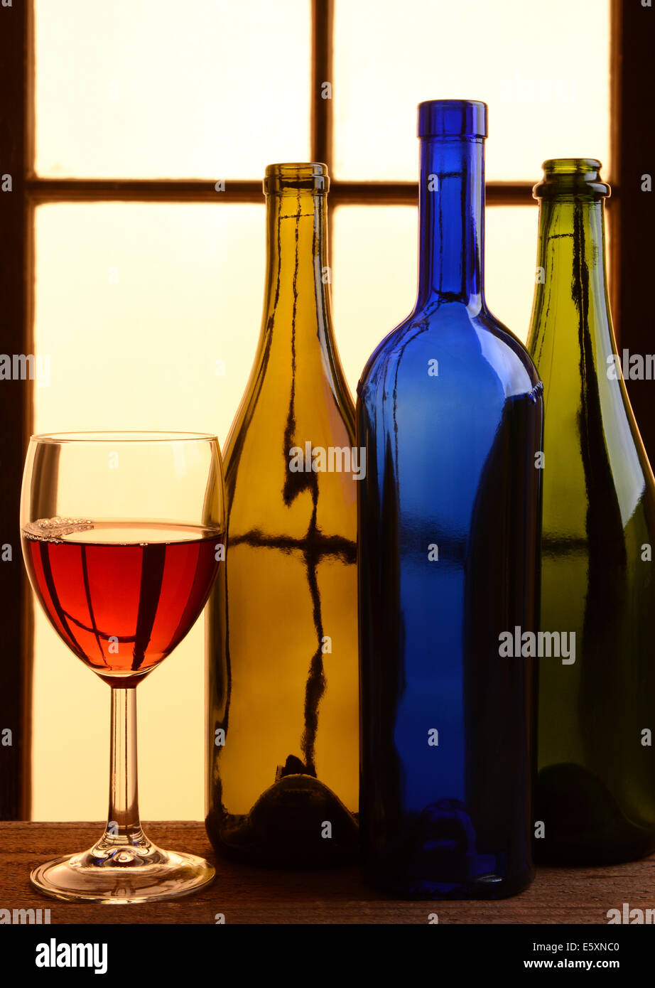 A wine still life with warm tones. Three different wine bottles and a glass of red wine in front of a window with - Stock Image