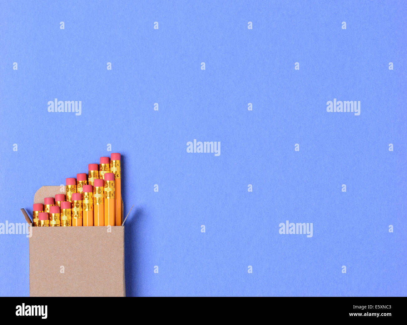 High angle shot of a box of new yellow pencils on a blue construction paper background. Horizontal format with copy - Stock Image