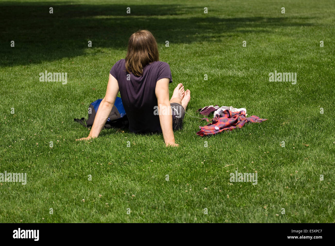 A man with long hair lies in green grass wearing a blue short sleeved shirt on a sunny day - Stock Image