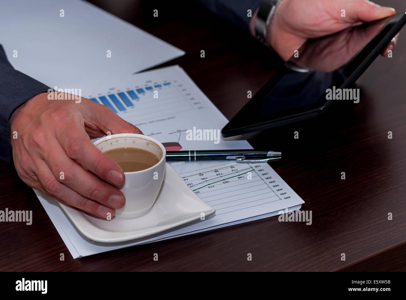 Man works in bussiness office with computer or laptop or notebook and papper graf and he drinks coffee Stock Photo