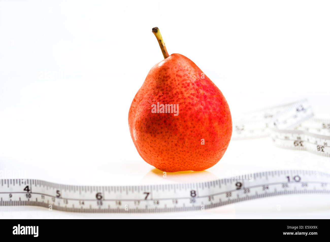 Red pear with tape measure.obesity, weight loss, dieting. - Stock Image