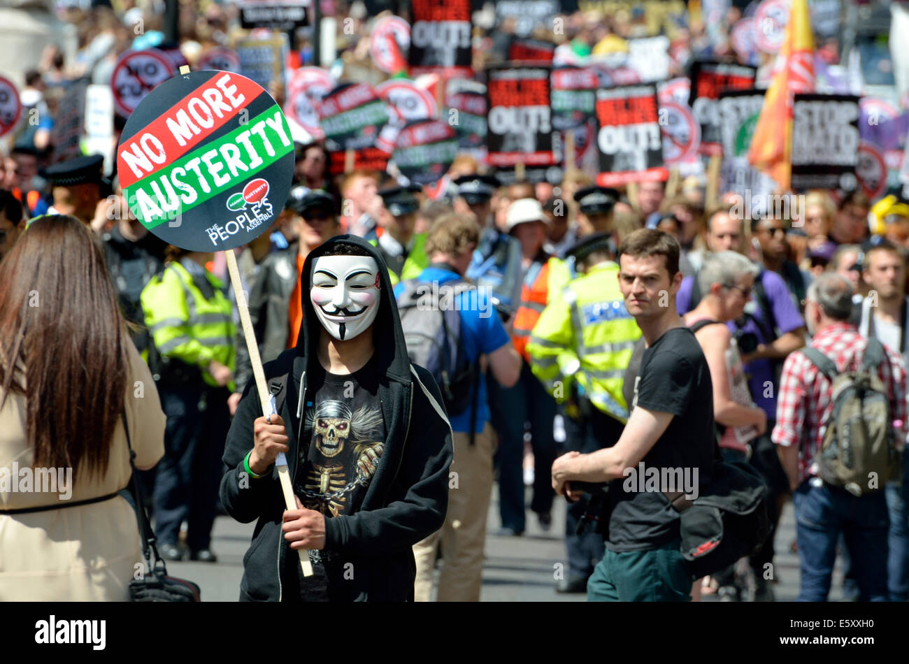 Protester on V mask with No Cuts placard at an anti-austerity march through London, 2014 - Stock Image