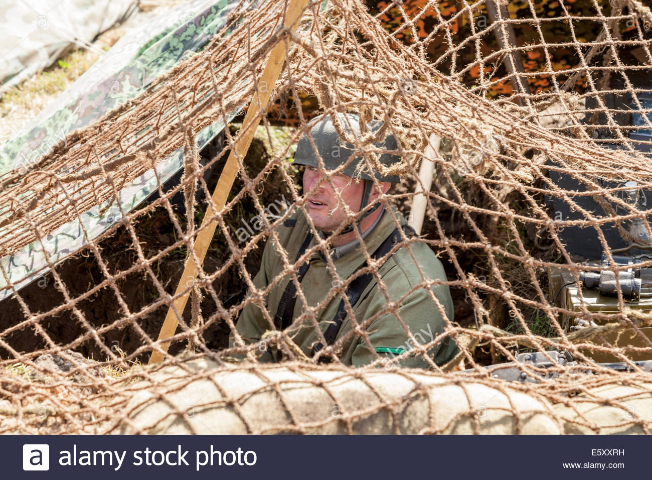 WW2 German soldier in a trench with camouflage netting - historical re-enactment - Stock Image