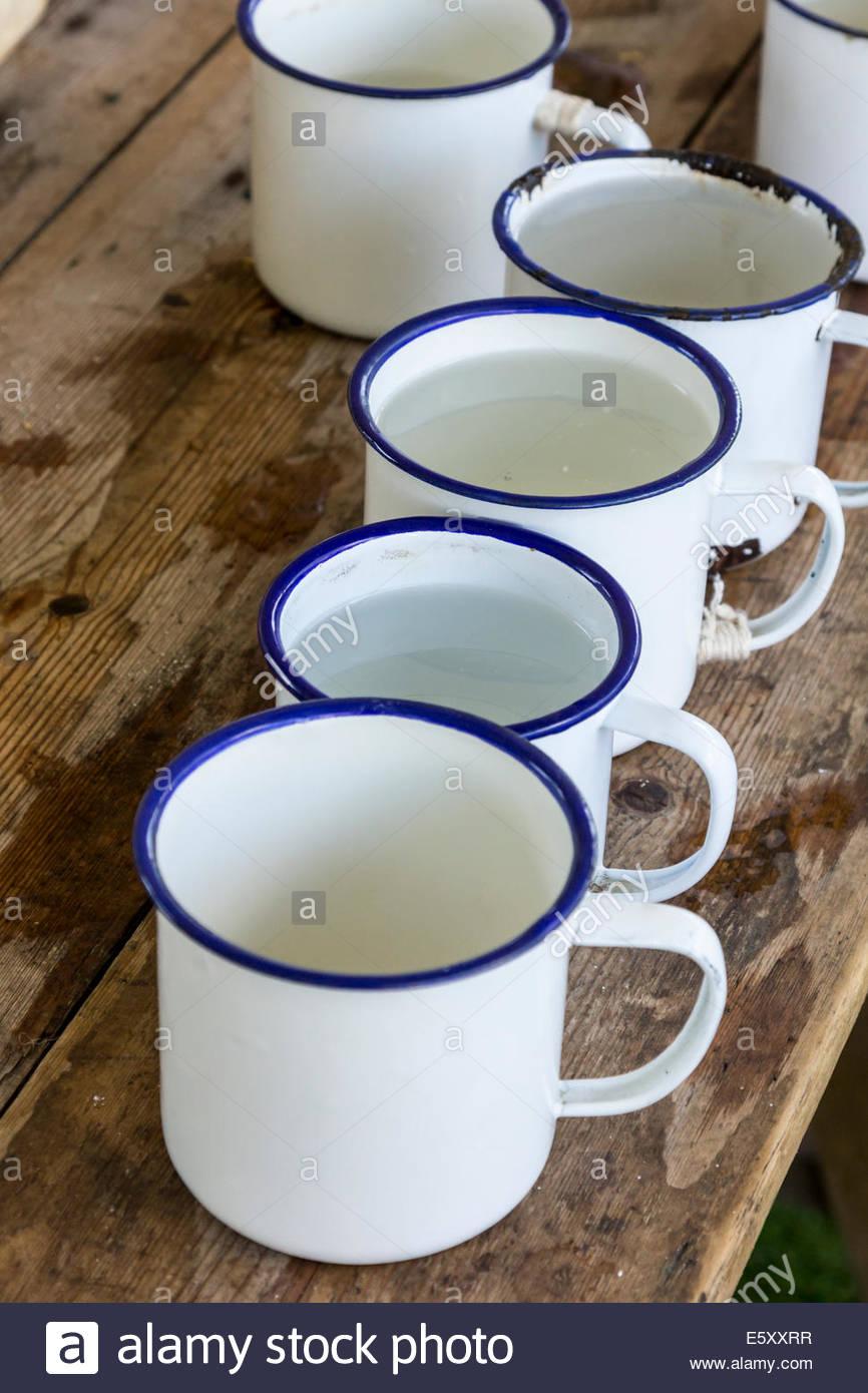 Row of enamel tin mugs - Stock Image