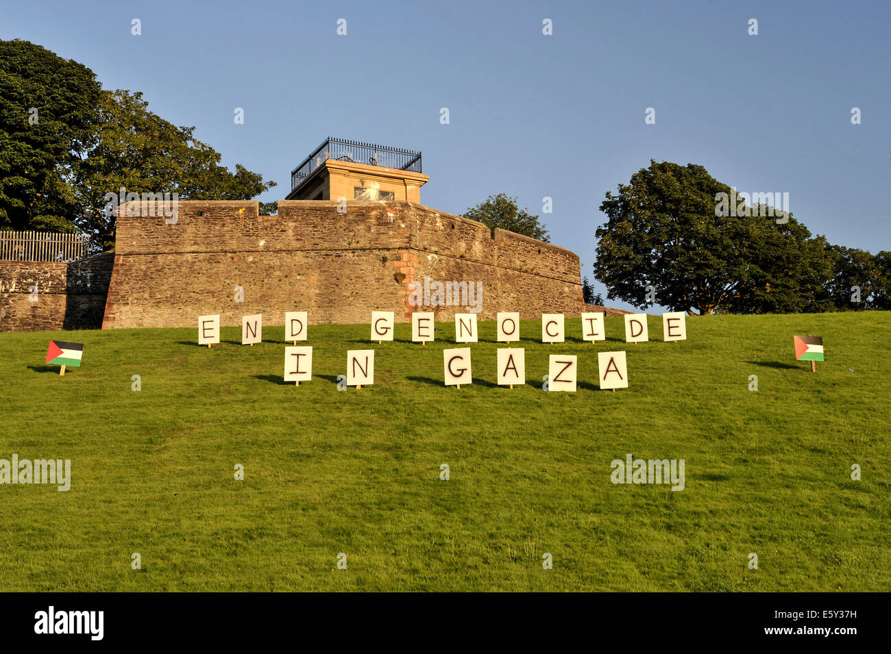 Placards on green outside of Walls of Derry, overlooking the Bogside, reads End Genocide in Gaza. Derry, Londonderry, - Stock Image