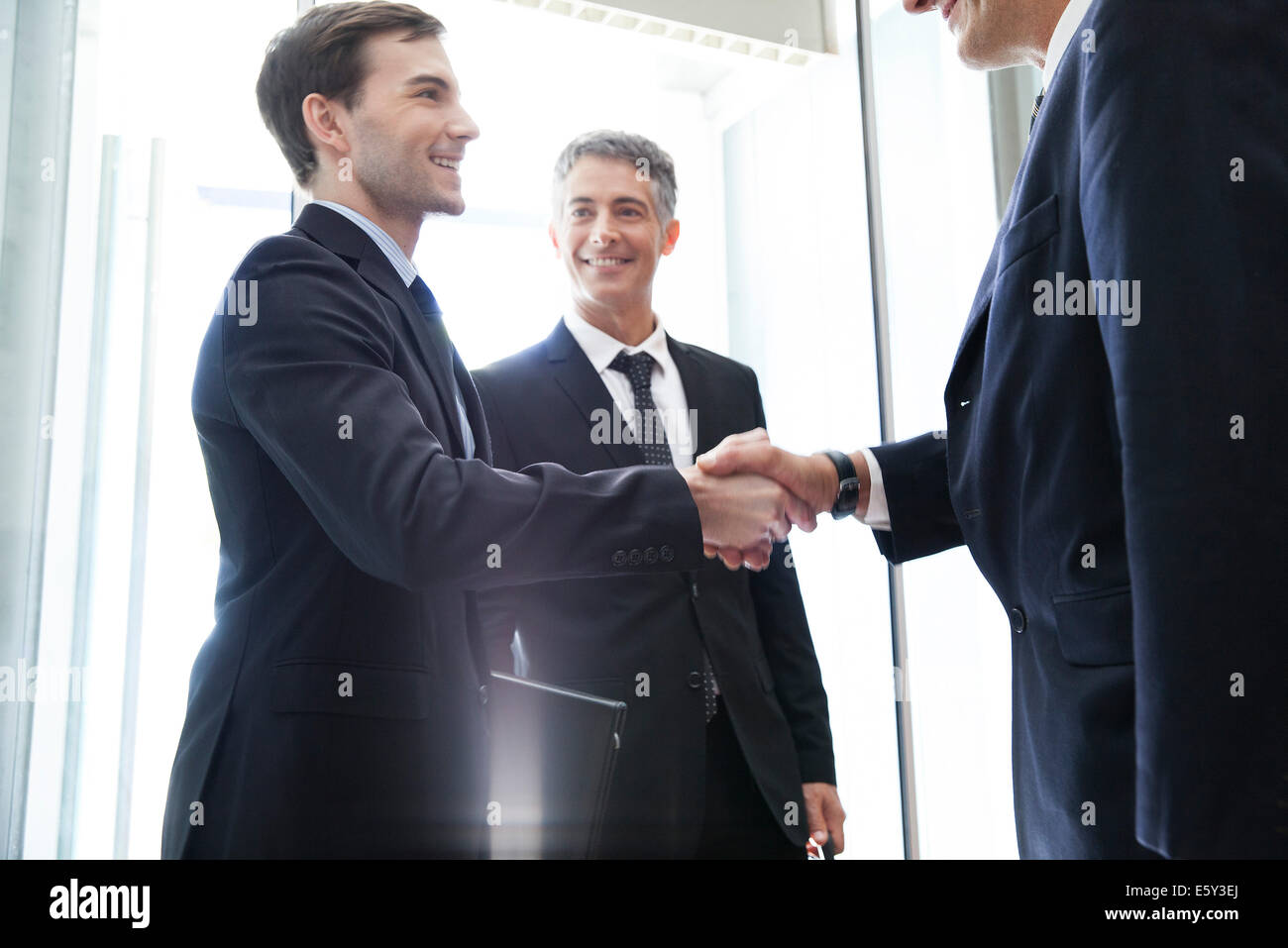 Young businessman shaking hands with senior associate - Stock Image