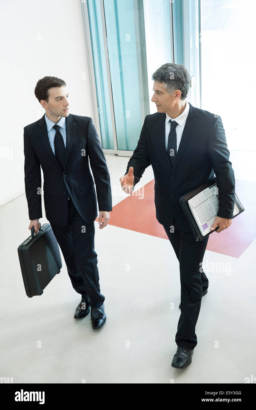 Businessmen passing through office building lobby together - Stock Image