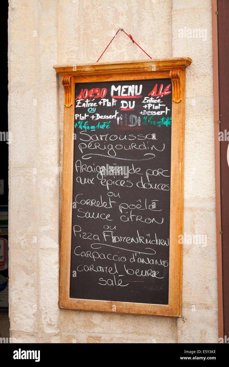 Chalk written French daily menu hanging on wall. - Stock Image