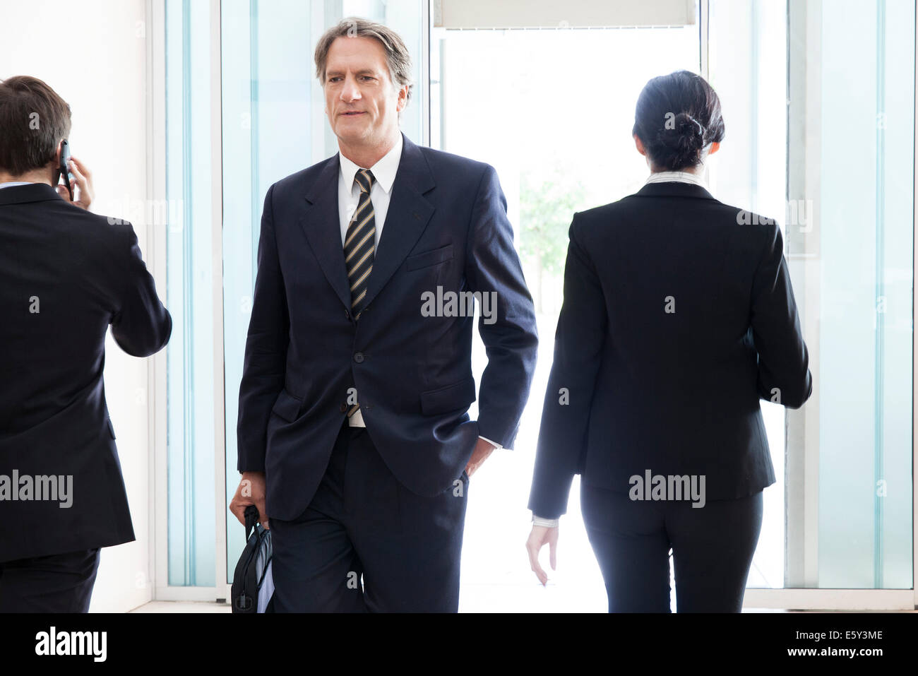 Businessman entering office building lobby - Stock Image