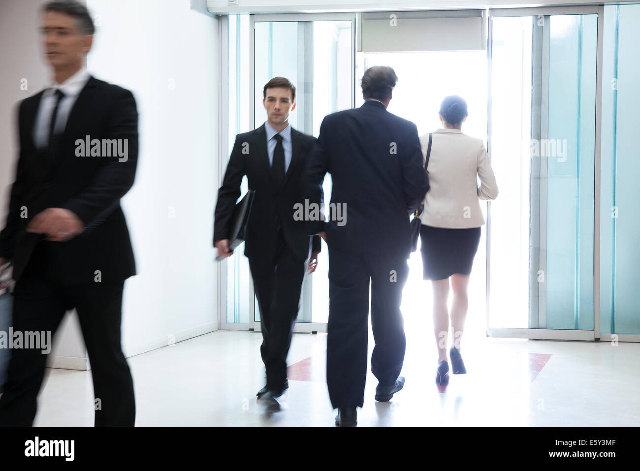 Business professionals passing through office building lobby - Stock Image